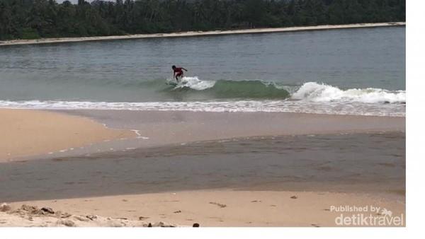 Seorang anak sedang berselancar di Pantai Mapaddaget