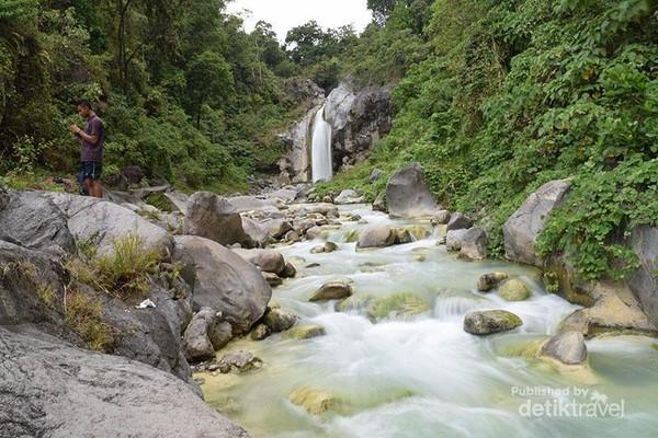 Aliran airnya berwarna hijau tosca dengan dihiasi ornamen bebatuan sungai di kanan dan kirinya.