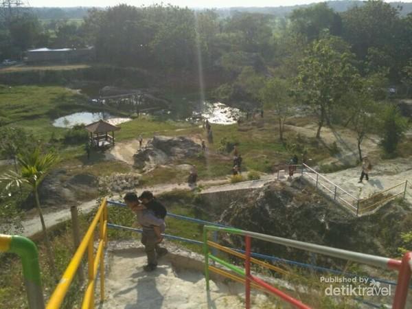 Pemandangan kolam serta beberapa pengunjung yang hendak menaiki tangga menuju puncak.