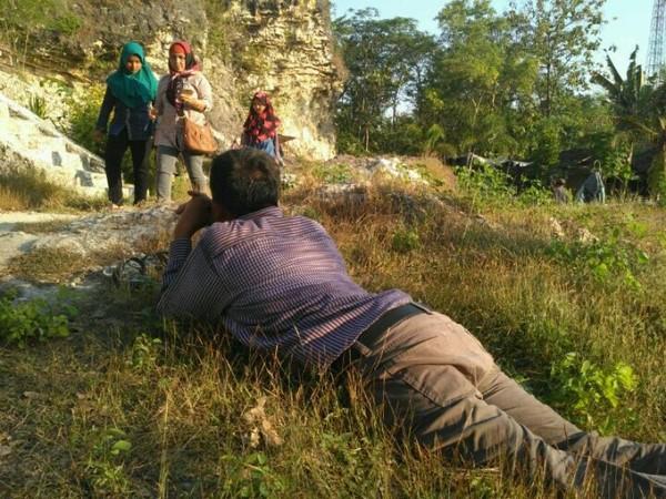 Salah satu pengunjung yang tengah menikmati keindahan Bukit Patrum dari atas rerumputan.
