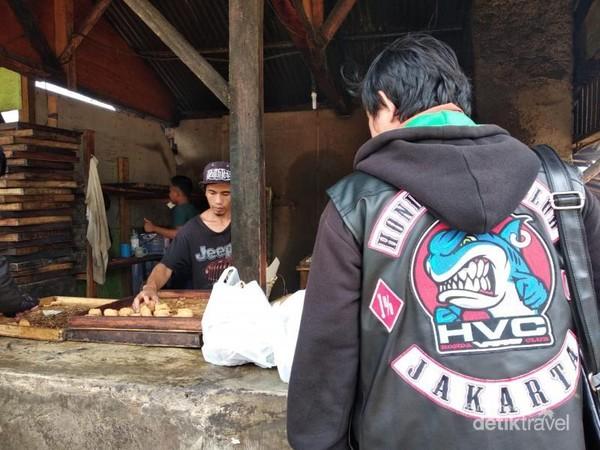 Salah satu pengunjung Desa Cileumbu membeli dan berkunjung ke pengolahan tahu Sumedang.