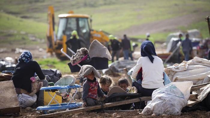 Palestinian Bedouin watch Israeli troops demolish tents and other structures of Khirbet Humsu hamlet in Jordan Valley in the West Bank, Wednesday, Feb. 3, 2020. (AP Photo/Majdi Mohammed)