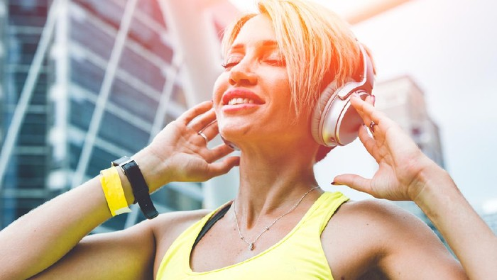 Sport woman happy enjoy with wireless music headphone urban outdoors background.
