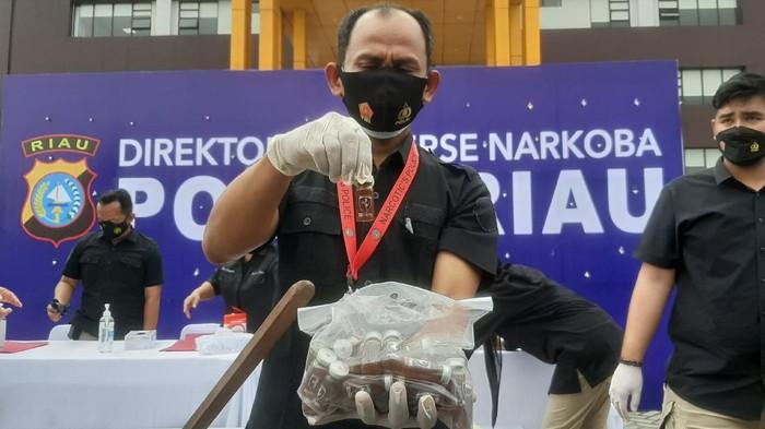 Polisi saat menunjukkan barang bukti liquid cair mengandung narkoba (Raja Adil/detikcom)