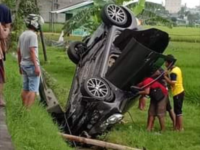 Sebuah mobil kecelakaan terperosok hingga nunging di selokan jalur ringroad utara Sragen, Kamis (4/2/2021).