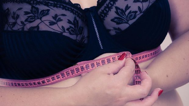 Plus size fat mature woman wearing bra with measure tape measuring her chest under breast. Closeup part of female body. Bosom, brafitting and underwear concept.