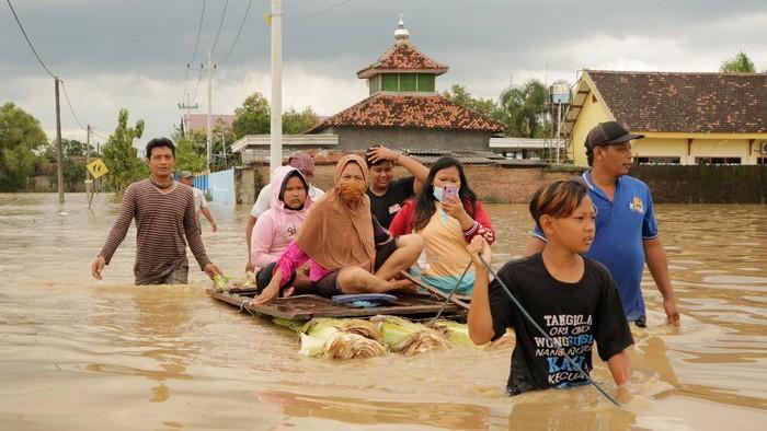 Warga mengevakuasi wanita lanjut usia saat banjir menggenangi Dusun Manisrenggo, Desa Gondangmanis, Kecamatan Bandar Kedungmulyo, Kabupaten Jombang, Jawa Timur, Jumat (5/2/2021). Banjir yang disebabkan meluapnya Sungai Konto dan Gude tersebut mengakibatkan tujuh Dusun di empat Desa Kecamatan Bandar Kedungmulyo tergenang banjir dengan ketinggian air mencapai 1,5 meter. ANTARA FOTO/Syaiful Arif/aww.