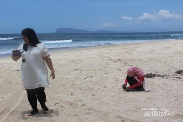 Pengunjung tengah menikmati pantai meski udara cukup panas.
