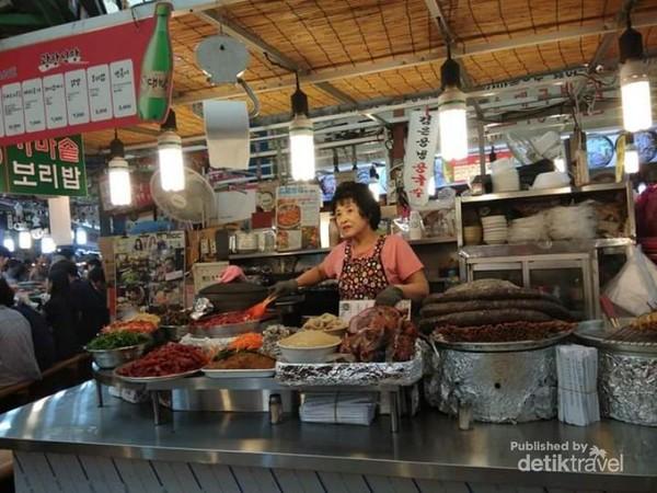 Seorang pedagang nampak sedang memasak dan melayani pelanggan.