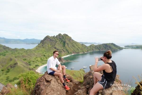 dua wisatawan asing sedang mengambil gambar di pulau padar
