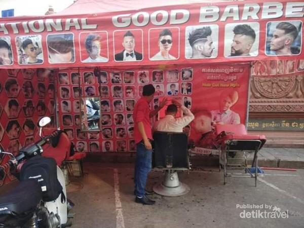 Aktivitas jasa potong rambut di tepi jalan samping sebuat kuil di pusat kota pun sudah mulai melayani pelanggannya