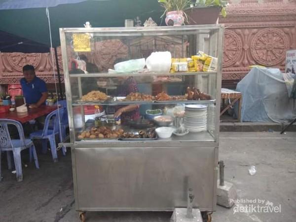 Tidak jauh dari kedai pangkas rambut, sebuah warung di tepi jalan yang sama mulai menjajakan masakan-masakan khas Phnom Pehn