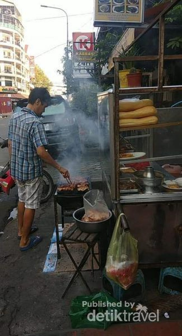 Seorang pedagang daging bakar sudah menyiapkan sajian untuk warga Phnom Penh di pagi hari. Sepiring nasi dan daging bakar plus segelas air putih dapat kita nikmati dengan harga USD 1