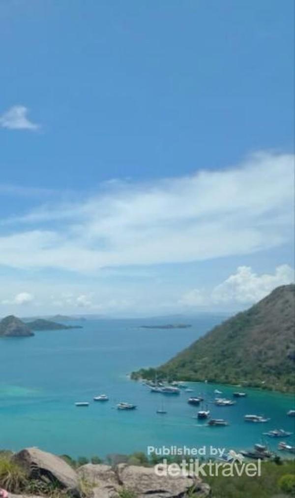 Foto dari Bukit Silvia dengan latar laut, bukit, dan kapal wisata