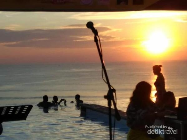 Pengunjung yang masih menikmati senja dan benerang bebas di tepian  Pantai Dreamland.