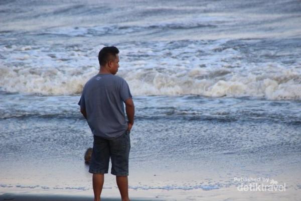 Salah seorang pengunjung yang tengah menikmati pantai.