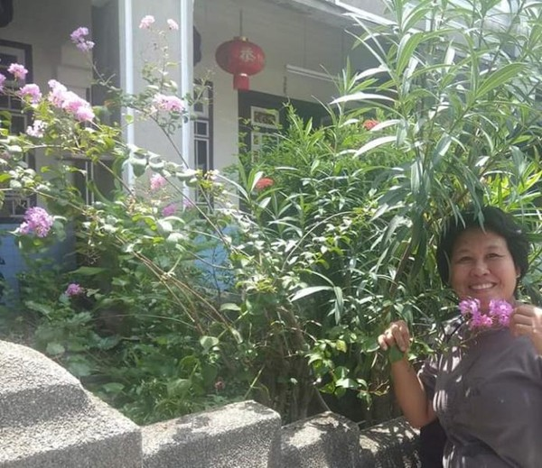 Berfoto di sebuah rumah klasik dengan taman bunga yang asri di Lebuh Acheh.