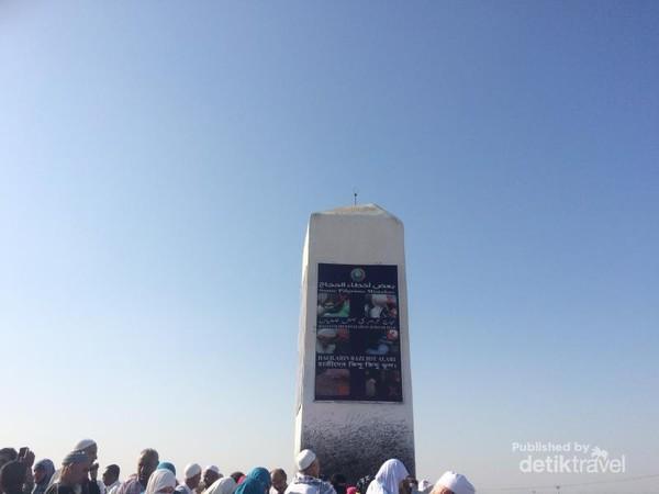 Monumen di puncak Jabal Rahmah yang dikelilingi wisatawan untuk berziarah