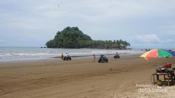 Pengunjung bermain-main di pantai yang landai.