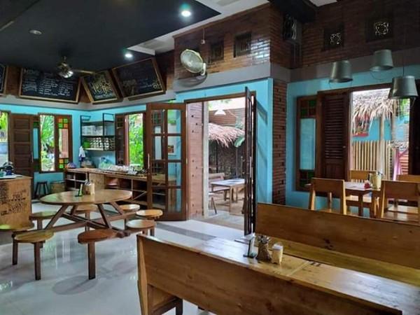 Pintu samping Cafe Kumpul Tjeret, perabotan kayu yang ditata apik menambah kenyamanan pengunjung