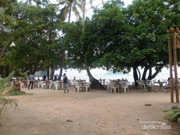 Suasana pantai dengan pepohonan yang teduh.