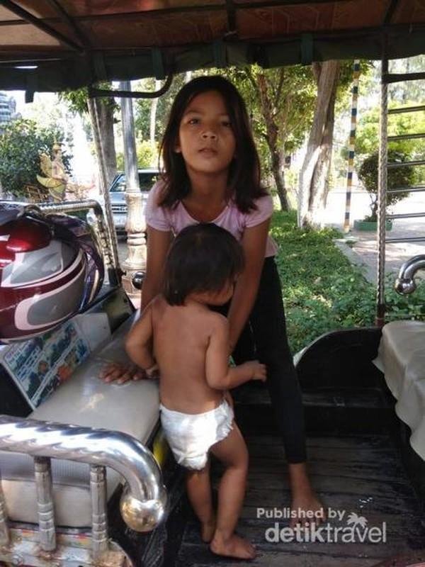 Anak-anak yang bermain di sekitar kuil pun mulai menaiki tuk-tuk yang parkir di dekat kuil.