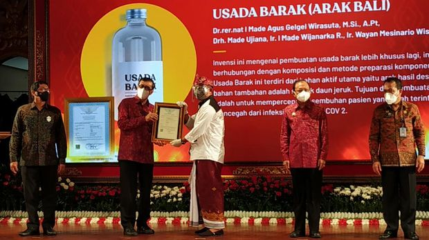 Menteri Hukum dan Hak Asasi Manusia (Menkumham) RI, Yasonna Hamonangan Laoly menyerahkan sertifikat hak kekayaan intelektual (HaKI) untuk kain tenun endek Bali di Taman Budaya Provinsi Bali, Jum'at (5/2/2021)