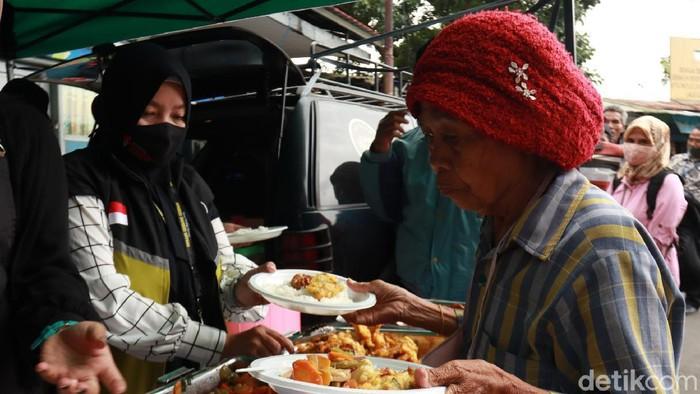 Sejumlah relawan membagikan 100 posi makan gratis kepada warga di kawasan Terminal Cicaheum, Kota Bandung.