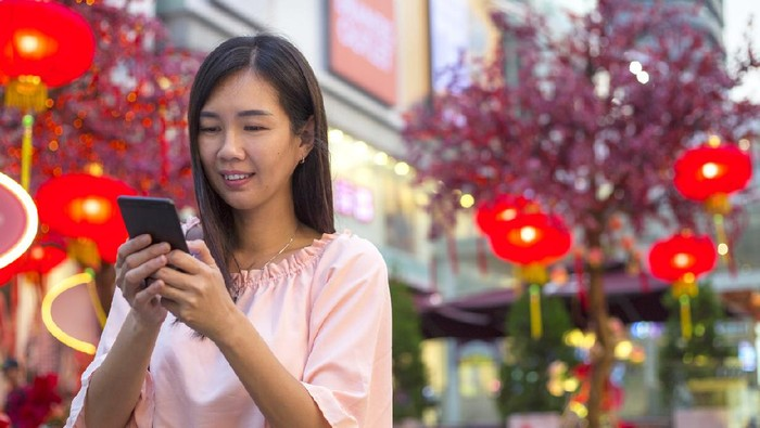 Asian woman standing at city steret decorated with lantern, sending greeting wishes with smart phone to the family and love one during Chinese new year
