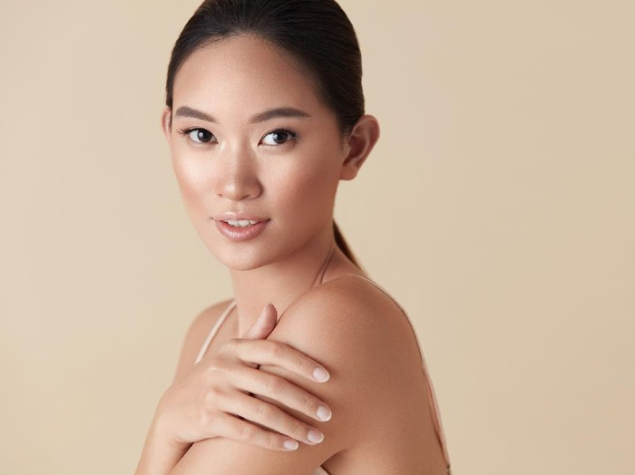 Skin Care. Asian Model Portrait. Young Woman With Closed Eyes Touches Face Against Beige Background. Female Enjoying With Healthy Glowing Skin After Daily Beauty Routine And Cosmetology Treatment.
