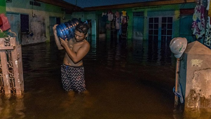 Seorang warga memasak di dalam rumahnya yang terendam banjir di Kelurahan Tanjung Mas, Semarang, Jawa Tengah, Sabtu (6/2/2021). Menurut data yang dihimpun Badan Penanggulangan Bencana Daerah (BPBD) Kota Semarang, sekitar 76 kelurahan yang tersebar di 10 kecamatan di Kota Semarang terendam banjir akibat curah hujan tinggi sejak Jumat (5/2) malam. ANTARA FOTO/Aji Styawan/wsj.