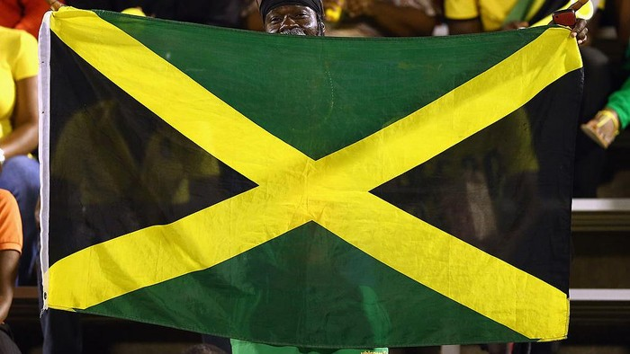 KINGSTON, JAMAICA - JUNE 07:  A fan waves a flag before the USA takes on Jamaica in the FIFA 2014 World Cup Qualifier at National Stadium on June 7, 2013 in Kingston, Jamaica.  (Photo by Streeter Lecka/Getty Images)