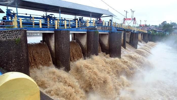 Warga memotret debit air yang deras di Bendung Katulampa, Kota Bogor, Jawa Barat, Minggu (7/2/2021). Badan Penanggulangan Bencana Daerah (BPBD) DKI Jakarta menyebutkan Bendung Katulampa berstatus siaga tiga dengan ketinggian muka air mencapai 130 cm akibat curah hujan tinggi di Bogor sehingga warga di bantaran sungai Ciliwung, Jakarta harus waspada terhadap potensi banjir. ANTARA FOTO/Arif Firmansyah/aww.