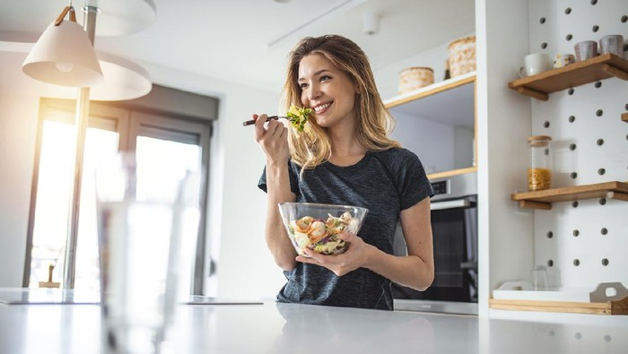 Photo of young woman enjoying a delicious salad while standing in her kitchen at home during the day.