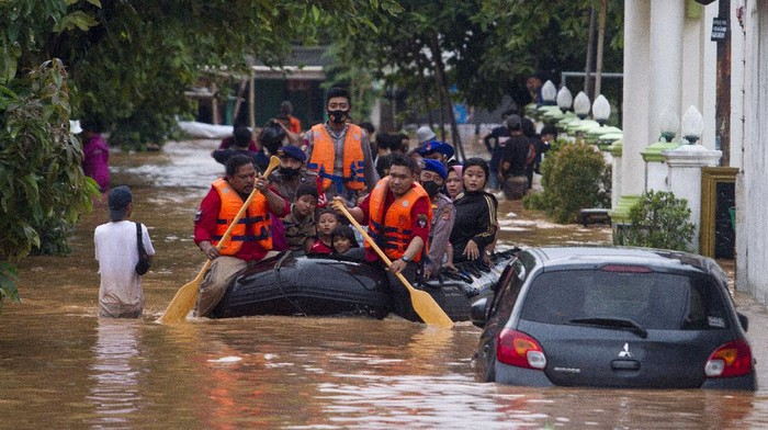Seorang warga menggendong anaknya melintasi banjir di ruas jalan Pantura, Jalan Ahmad Yani, Cikampek, Karawang, Jawa Barat, Minggu (7/2/2021).  Hujan yang terjadi di wilayah tersebut mengakibatkan sejumlah ruas jalan tergenang banjir dan menimbulkan kemacetan. ANTARA FOTO/M Ibnu Chazar/rwa.
