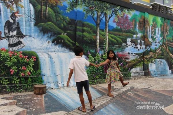 Anak-anak berfoto di lukisan 3 dimensi yang terdapat di sepanjang tembok.