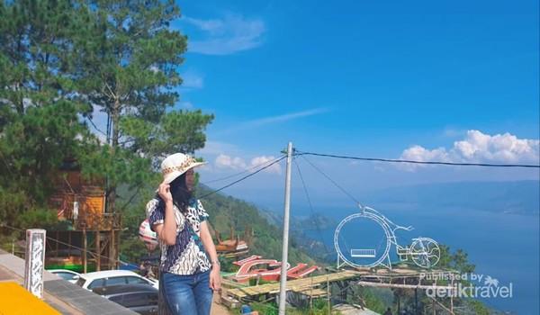 Tak ada salahnya memakai topi agar semakin nyaman menikmati pemandangan Danau Toba.