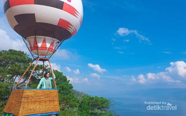 Menaiki replika balon udara dengan latar Danau Toba.