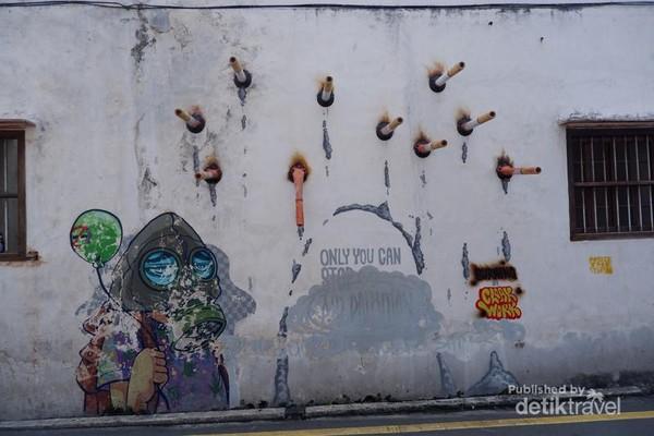 Street art orang yang mengenakan masker agar terhindar dari bahaya asap rokok.