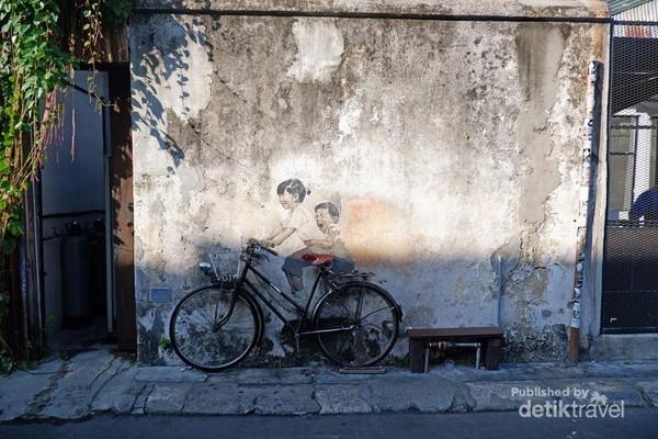 Sebuah lukisan 2 orang anak yang saling berboncengan di sebuah sepeda.