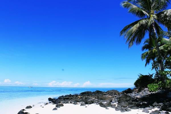 langit yang biru, pasir putih dan lembut dan air laut yang jernih tanpa ombak