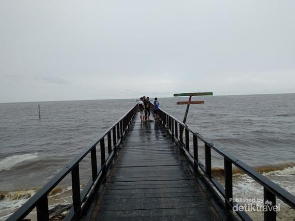 Jembatan kayu yang mengarah ke laut hitam.
