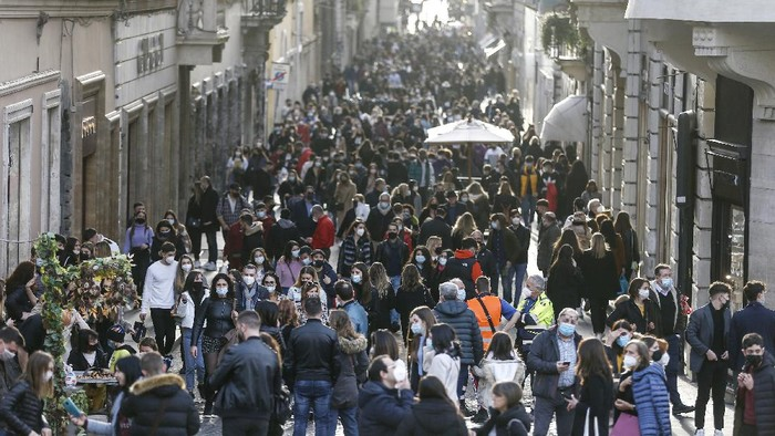 People crowd Via Condotti shopping street in Rome, Saturday, Feb. 7, 2021 following the ease of restriction measures to curb the spread of COVID-19. (Cecilia Fabiano/LaPresse via AP)