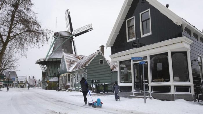 Seorang wanita menarik anaknya di atas kereta luncur di Zaandam,  Amsterdam, Belanda, Minggu (7/2/2021).  Belanda tengah dilanda badai salju yang diketahui menjadi badai besar pertama dalam satu dekade.