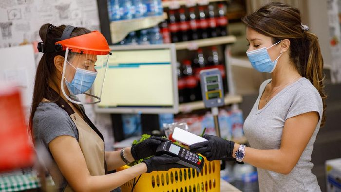 Female customer doing a contactless payment at the supermarket
