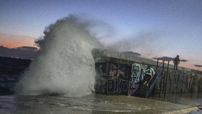 A young women goes down the stairs as a wave hits a wave-lashed breakwater during a windy afternoon in the southern Athens coastal suburb of Flisvos, on Monday, Feb. 8, 2021. A cold and strong winter weather hit Europe with temperatures far below zero. (AP Photo/Petros Giannakouris)