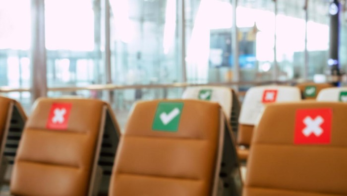Social distancing, Blurred image of empty chairs in an airports departure area marked with symbols regarding social distancing protocol to prevent the spreading of novel corona virus, COVID-19