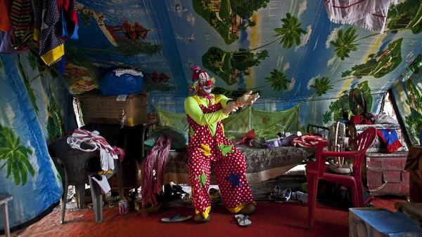 Mengenakan jumpsuit polkadot merah, dengan riasan mencolok dan coretan cat putih di wajahnya, para pemain sirkus siap memulai pertunjukan.