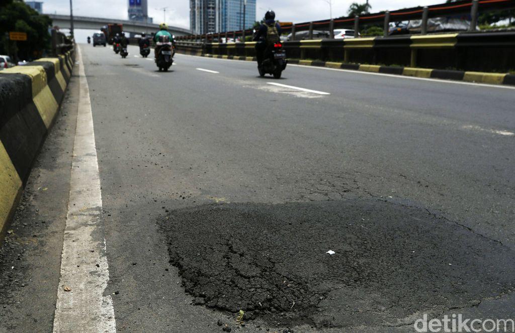 Hujan mulai sering mengguyur Jakarta. Kerusakan jalan raya di ibukota pun kian parah, seperti terlihat di Jalan Gatot Subroto, Selasa (9/2/2021).