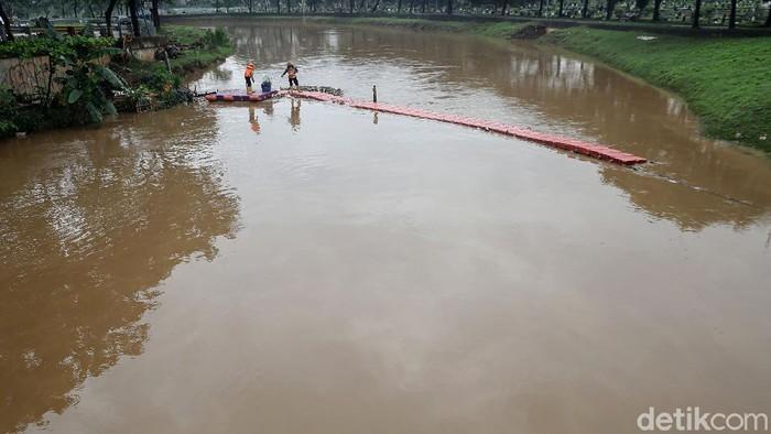 Petugas Pekerja Penanganan Sarana dan Prasarana Umum (PPSU) terus berupaya membuat Kali Pesanggrahan tetap bersih bahkan di musim hujan.